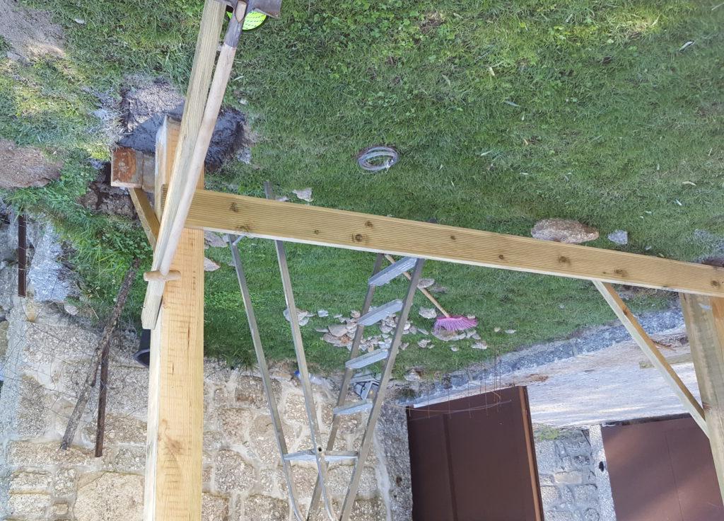 Os dois primeiros postes levantados, alinhados, aprumados e ancorados, com massa a secar